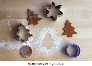 Christmas tree form sprinkled with flour on the table with dough and cutter forms