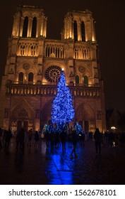 Christmas tree in front of the Notre Dame cathedral in the evening. Paris, France. 2018 last Christmas old photo before a fire in April 2019. Tourists silhouettes. Beautiful reflection.