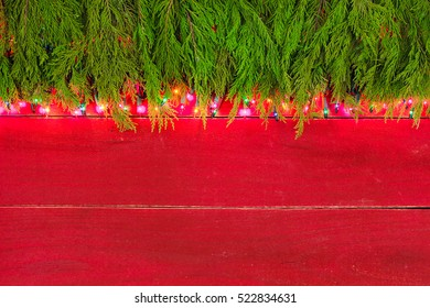 Christmas tree garland border with colorful string of lights on antique red rustic wood background; Christmas background with red copy space