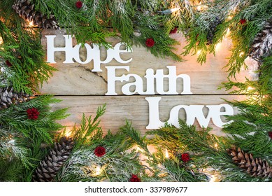 Christmas tree garland border with snow, lights, and the words Hope, Faith, Love on antique rustic wooden background