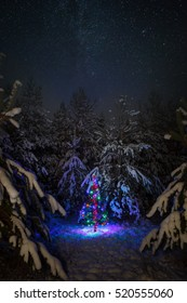 Christmas tree with garlands on a background of the night sky and the Milky Way in winter forest.