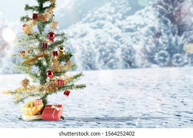 Christmas tree with gift box on snow with snowy hill background