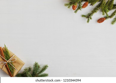 Christmas tree, gift and cones on a white wooden table. Preparation for writing the text, copy space.