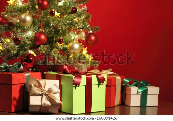 Christmas tree with gifts on red background.