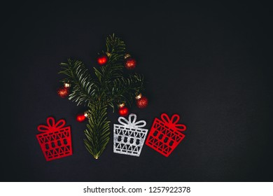 Christmas tree and gifts symbols over black background with fir tree, red christmass balls, top view. Flat inspiring holidays layout.