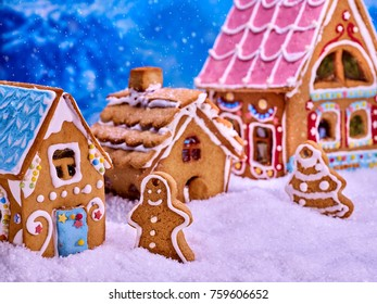 Christmas tree with gingerbread man cookies and sweet houses village with Xmas glaze food.