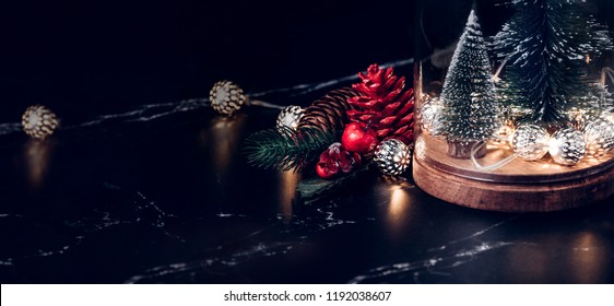 Christmas tree and glowing light string and pine cone and mistletoe decoration on marble table and blue background.Winter holiday greeting card.banner for display of design or content
