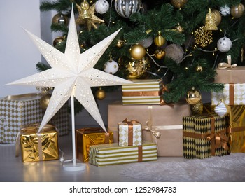 Christmas tree with gold gifts in the room Christmas. Beautifully decorated house with a gold tree and presents at Christmas.