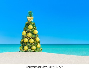 Christmas tree with golden balls and beads decorations at tropical ocean beach. New Year vacation in hot countries greeting card