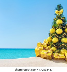 Christmas tree with golden balls and fancy gift boxes with bows at tropical sandy beach against ocean. New Year holidays in hot countries concept, square greeting card with space for your text