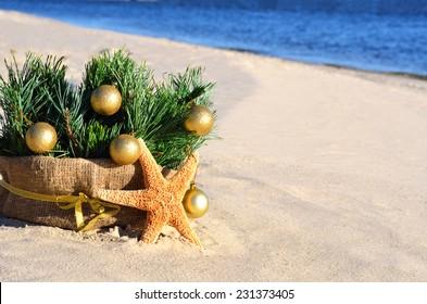 Christmas tree with golden christmas balls and starfish on the sand on the beach
