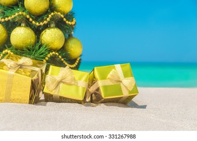 Christmas tree with golden decorations and packed gift boxes close-up at tropical ocean beach. New Years vacation in hot countries background concept
