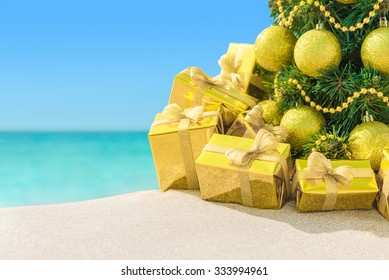 Christmas tree with golden decorations and packed gift boxes close-up at tropical sandy ocean beach. New Years vacation in hot countries background concept