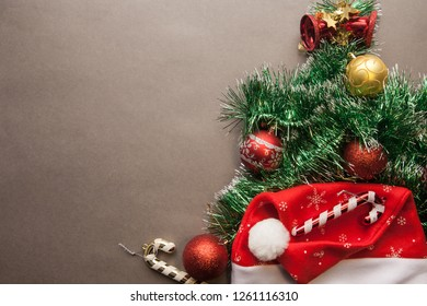 Christmas tree of green garland with Santa's hat and red balls on a gray background