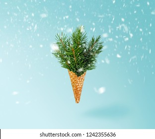 Christmas Tree Ice Cream Cone Levitation in Snow on Ligth Blue Background. New Year Concept. Minimal Holiday Composition
