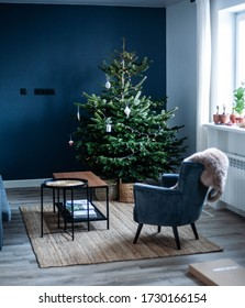 Christmas tree in the interior. Scandinavian style, minimalism. Dark blue wall, grey chair, braided baskets. White paper origami toys.