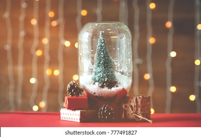 Christmas tree in jar with snow and presents under it. Xmas lights on background.