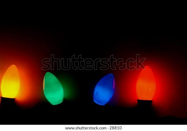 : Christmas Tree Lights - Four Glowing Bulbs - Black Background