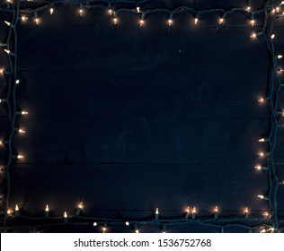 A Christmas tree lights frame over a black wooden surface great for writing text or background