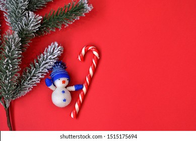 Christmas tree little toy snowman with crochet striped candy lollipop on the red background top view. Imitative fir-tree as a symbol of new year and winter holidays card picture. Flat lay card