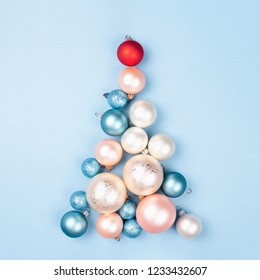 Christmas tree made of Christmas balls on blue background. Minimal New year concept.