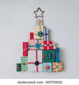 Christmas tree made of colorful presents and gifts. Flat lay. Holiday concept.