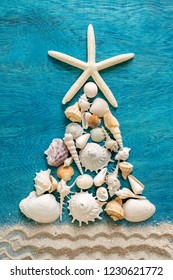 Christmas tree made from different type of sea shells and starfish with sand decoration on blue wooden background, top view, vertical composition