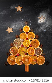 Christmas tree made of dried oranges, cinnamon, cranberries, nuts and star anise on dark background. Viewed from above, vertical composition