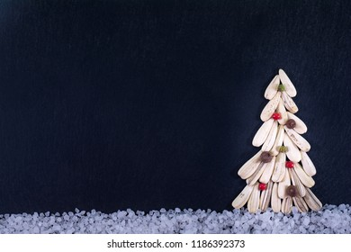 Christmas tree made with dry sunflower seed with colorful pepper, on a slate background.
