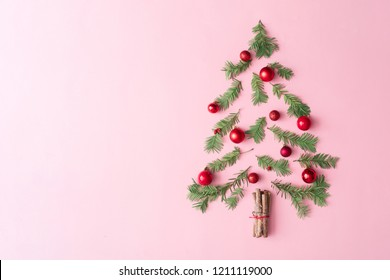 Christmas tree made with evergreen fir, bauble decoration and cinnamon sticks on pastel pink background. Minimal holiday flat lay table compoition with copy space.