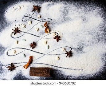 Christmas tree made of flour, decorated with anise star, dry orange peel, cinnamon stick and small candies