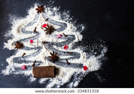 Christmas tree made from flour on a black background with anise stars and cinnamon sticks