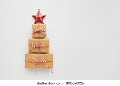 Christmas tree made of gift boxes and decorative star on white background. Top view, flat lay, copy space. - Shutterstock ID 1835390026