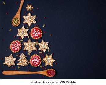christmas tree made from gingerbread cookies and wooden spoons with spices on dark blue background with copy space for text. holiday, celebration and cooking concept. new year and christmas postcard