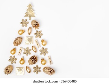 christmas tree made from golden winter decorations on white background with empty copy space for text. holiday and celebration creative concept. new year and christmas postcard or invitation. top view