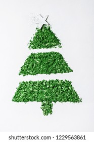Christmas tree made of green eye shadow with a star on top on a white surface.
