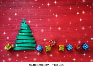 Christmas tree made from green ribbon with small gifts on red background. Copy space