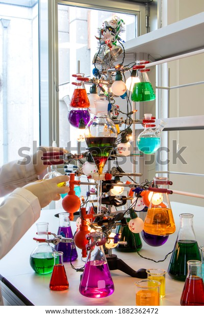 Christmas tree made of iron, filled tubes, conical flasks, erlenmeyer with colorful liquids used in chemistry. New year in the chemistry laboratory concept.