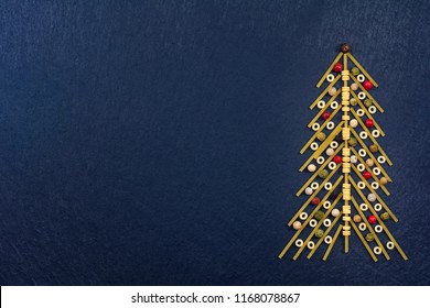 Christmas tree made with italian spaghetti with colorful pepper, on a slate background.