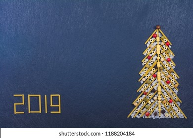 Christmas tree made with italian spaghetti with colorful pepper and salt, on a slate background.