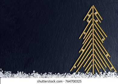 Christmas tree made with italian spaghetti with salt on a slate background.