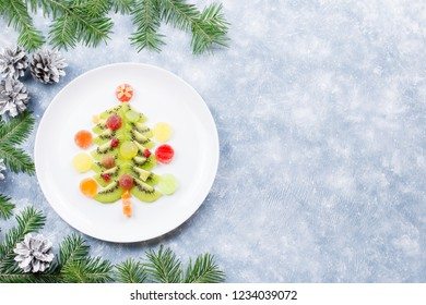 Christmas tree made of kiwi and fruit jelly on a plate with fir branches and decorations. Top view, copy space
