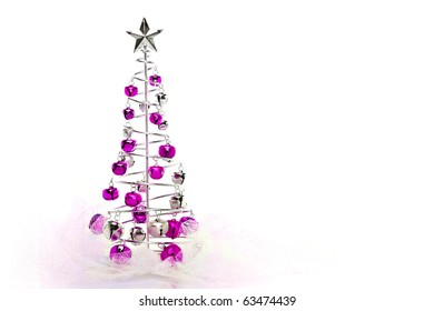 Christmas tree made out of pink and silver jingle bells on pink shimmery fabric