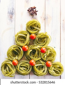 A christmas tree made with pasta nests and tomatoes
