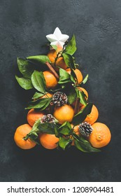 Christmas Tree made of tangerines and pine cones on black concrete background. Top view. Christmas and New Year Holidays concept