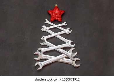 Christmas tree made of tools. Wrenches spanners on black background. Industrial greeting card and happy new year creative concept.