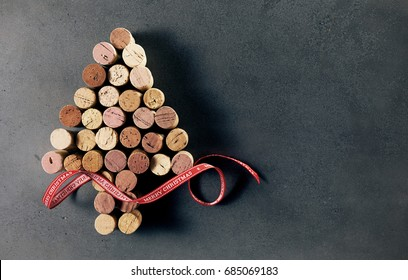 A Christmas tree made of used wine bottle corks with a red decorative ribbon, isolated on a dark background with copy space.