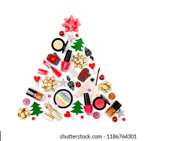 Christmas tree made from winter decorations and cosmetic products on white background. Holiday and celebration creative concept. Flat lay, top view
