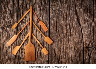 Christmas tree made from wooden kitchen tools and utensils on rustic wooden background with copy space. Flat lay background