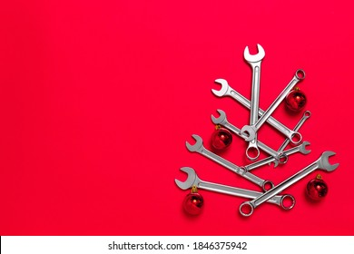 Christmas tree made of wrenches decorated with balls on a red background. New Year banner with tools. Postcard with place for greeting text for happy new year with industrial holiday concept. Close-up